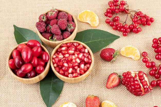 Kommen met granaatappel, frambozen en heupen met verspreid assortiment fruit Gratis Foto
