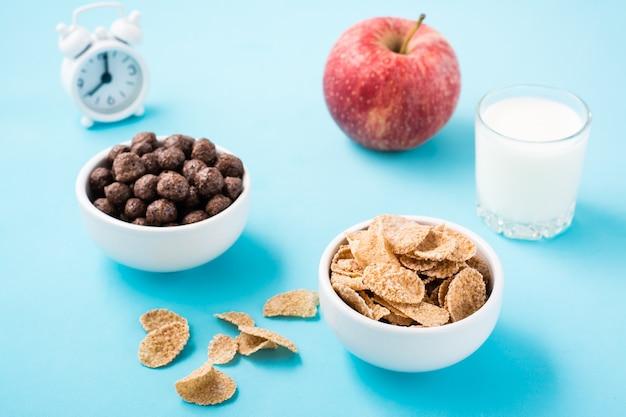 Kommen met granen en chocolade ballen, een glas melk, een appel en een wekker op een blauwe tafel. gepland ontbijt