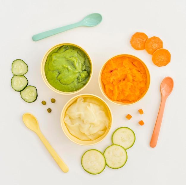 Kommen met groentenpuree voor baby en lepels