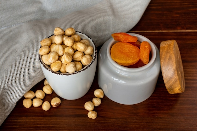 Kommen met hazelnoot en gedroogde abrikozen op houten tafel. gedroogd fruit en noten concept
