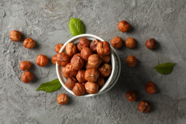 Kommen met hazelnoten op grijze tafel, bovenaanzicht. vitamine voedsel