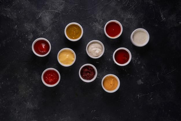 Kommen met heerlijke sauzen op zwarte rustieke achtergrond. bovenaanzicht