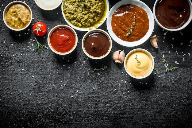 Kommen met heerlijke sauzen. op zwarte rustieke tafel