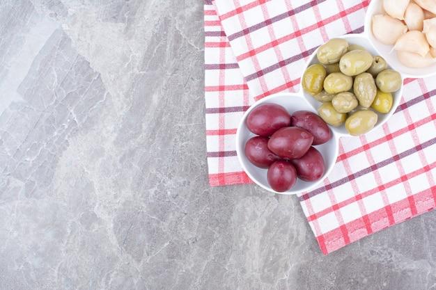 Kommen met ingelegde pruimen, olijven en knoflook op tafelkleed.
