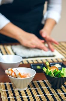 Kommen met ingrediënten voor sushi en chef-kok achter het verspreiden van rijst op nori-zeewier