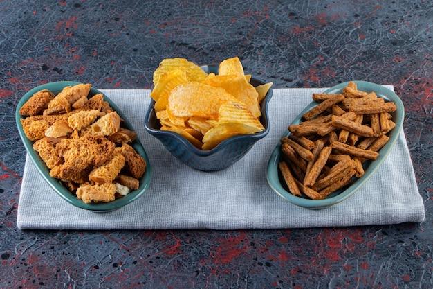 Kommen met lekkere chips en knapperige crackers op een donkere ondergrond.