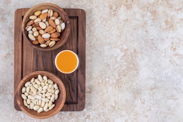 Kommen met noten en een kopje sap op een bord
