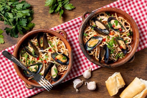Kommen met pasta en smakelijke mosselen