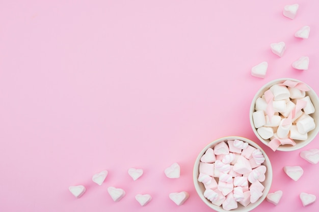 Kommen met schuimgebakje op roze achtergrond