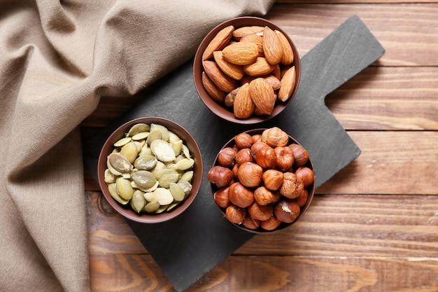 Kommen met verschillende gezonde noten op houten oppervlak
