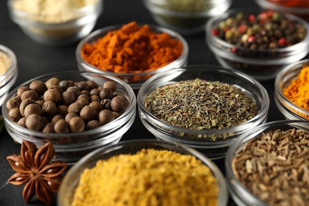 Kommen met verschillende kruiden en ingrediënten op zwart