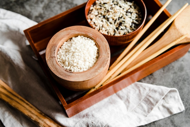 Kommen met verschillende rijst en houten eetstokjes