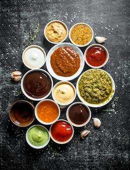 Kommen met verschillende sauzen. op donker rustiek