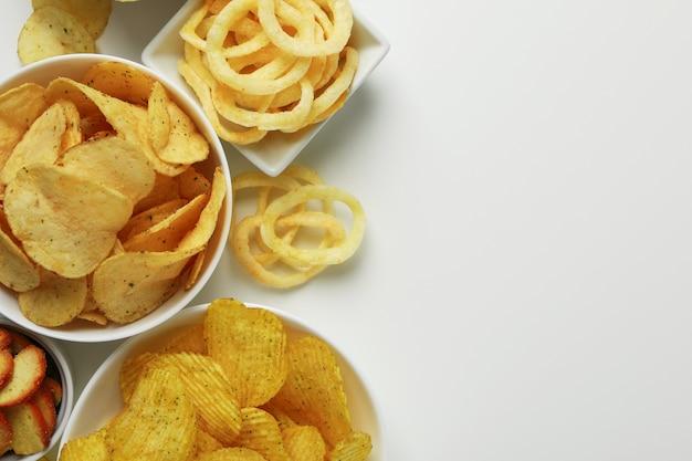 Kommen met verschillende snacks op wit