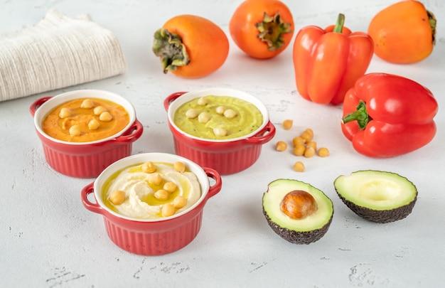 Kommen met verschillende soorten hummus: klassiek, avocado en paprika-persimmon