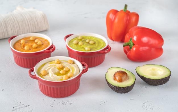 Kommen met verschillende soorten hummus: klassiek, avocado en paprika