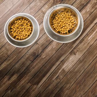 Kommen met voedsel voor huisdieren op de vloer