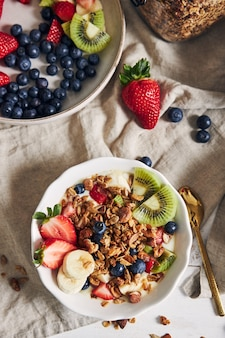 Kommen muesli met yoghurt, fruit en bessen op een wit oppervlak