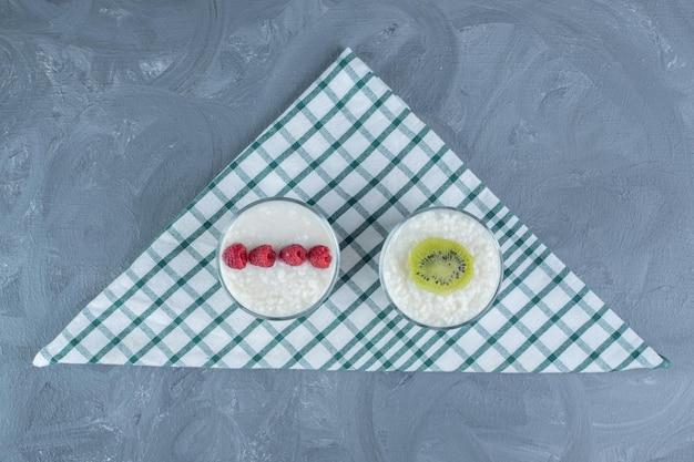 Kommen rijstpudding gegarneerd met frambozen en kiwiplak op een tafelkleed op marmeren tafel.