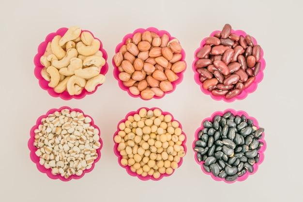 Kommen sojaboon, zwarte bonen, leesboon, pinda, cashewnoot en gierst op de witte tafel.