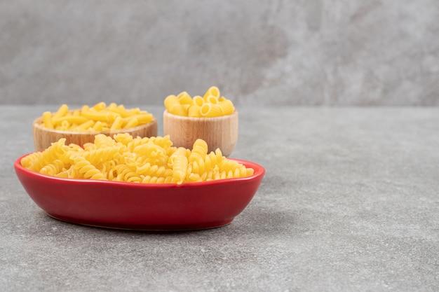 Kommen van verschillende ongekookte pasta op marmeren oppervlak