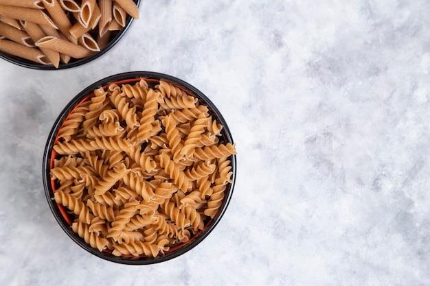 Kommen vol met ongekookte penne rigate en fusilli-pasta op marmer