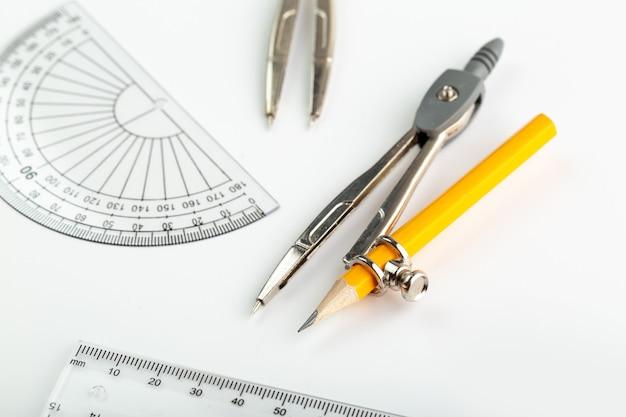 Kompas en andere tekeningscijfers die op wit bureau worden geïsoleerd