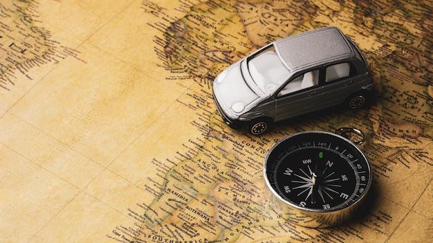 Kompas en miniatuurautostick speelgoed op een antieke kaart. - reis- en avonturenconcept.