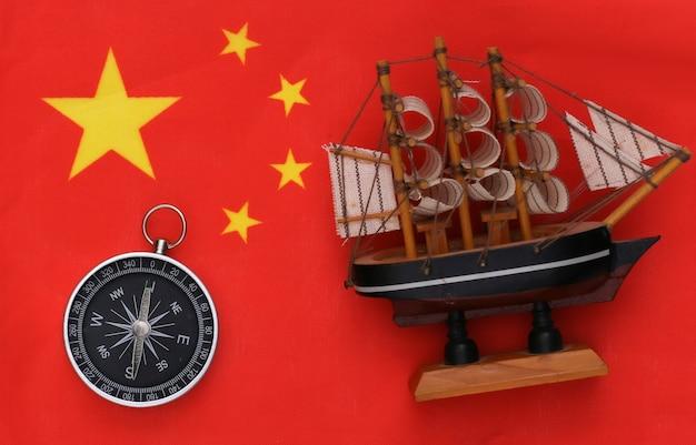 Kompas en schip op de vlag van china close-up. reizen, vrachtvervoer of avontuur concept. bovenaanzicht