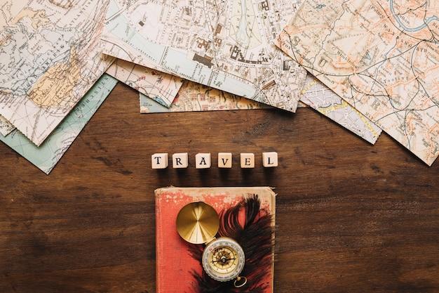 Kompas en veer in de buurt van schrijven en kaarten