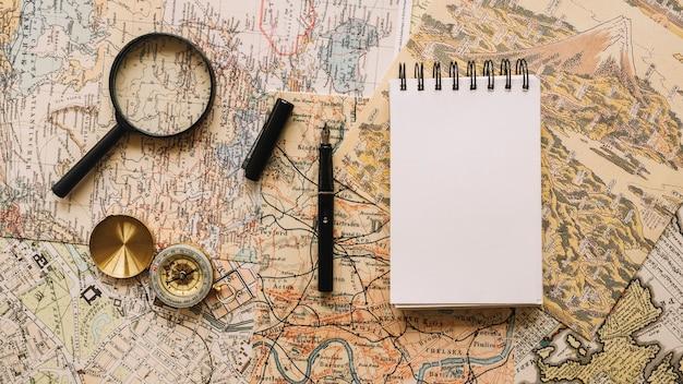 Kompas en vergrootglas dichtbij notitieboekje en pen