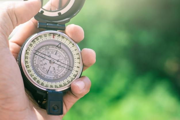 Kompas houden op onscherpe achtergrond. achtergrond of reisafbeelding van een achtergrond of navigator gebruiken.