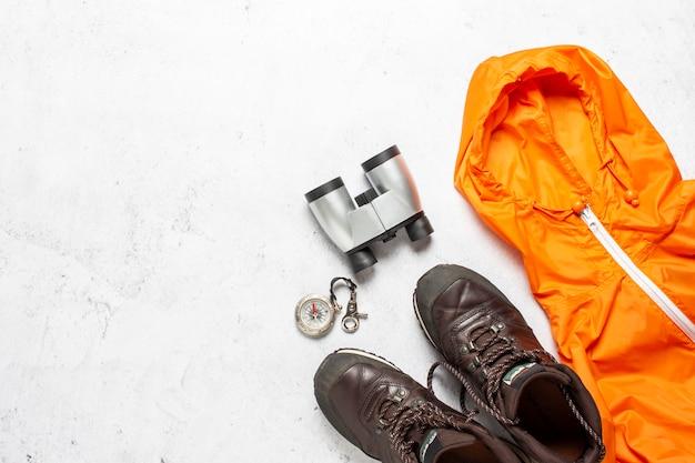 Kompas, laarzen, jas en verrekijker op een concrete achtergrond. concept van wandelen, toerisme, kamp, bergen, bos, sport oriëntatie.