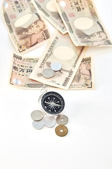 Kompas met japanse yenbankbiljetten en japans yenmuntstuk op witte achtergrond
