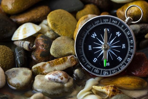Kompas op de kiezels en shell bij rivieroever. concepten van toerisme en avontuur.