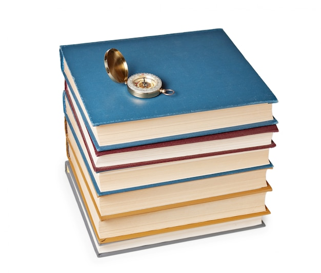 Kompas op een stapel boeken geïsoleerd op een witte achtergrond