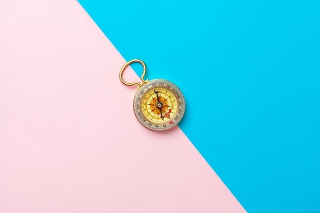 Kompas op roze en blauwe achtergrond, bovenaanzicht