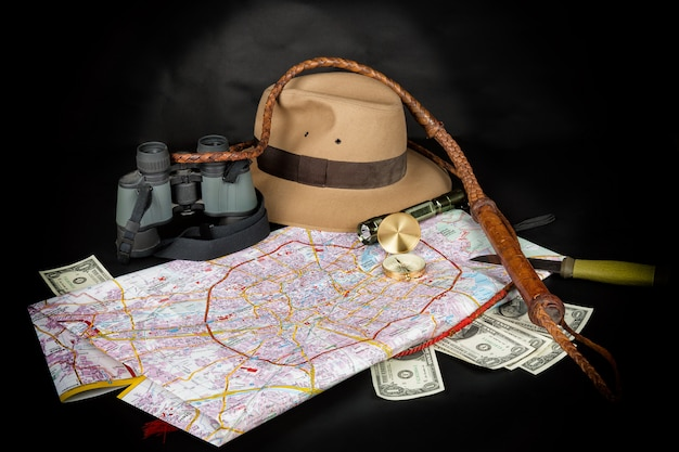 Kompas op stadsplattegrond met zaklamp, fedora hoed, bullwhip, verrekijker, mes en dollarbiljetten