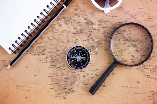 Kompas op vintage kaart met vergrootglas en boek. plan reizen en avontuur concept.