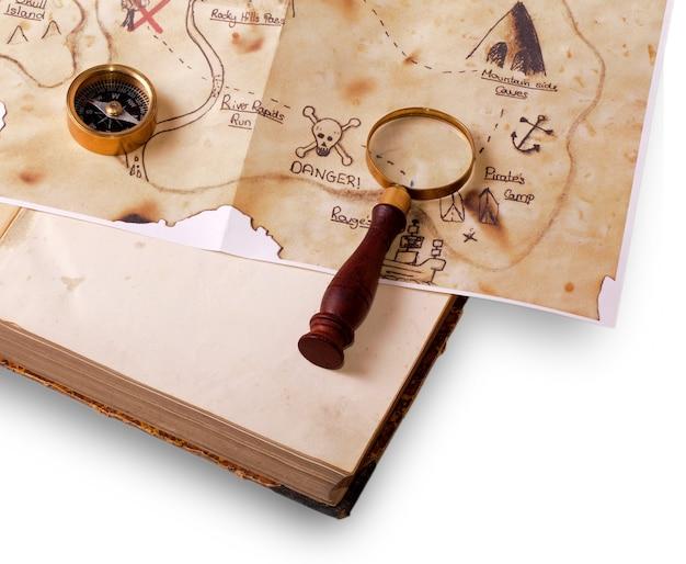 Kompas, vergrootglas en kaart op het oude boek