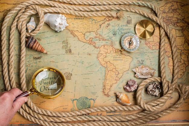 Kompas, vergrootglas en touw op vintage kaart