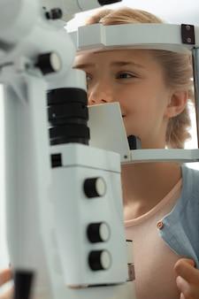 Komt naar de dokter. schattig tienermeisje met donkere ogen voelt zich goed als ze naar de oogarts gaat