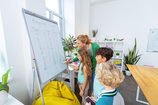 Komt naar schoolbord. ijverige studenten komen naar schoolbord terwijl ze afvalsortering bestuderen terwijl ze in de buurt van de leraar staan