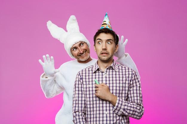 Konijn beangstigend dronken man over paarse muur. verjaardagsfeest.