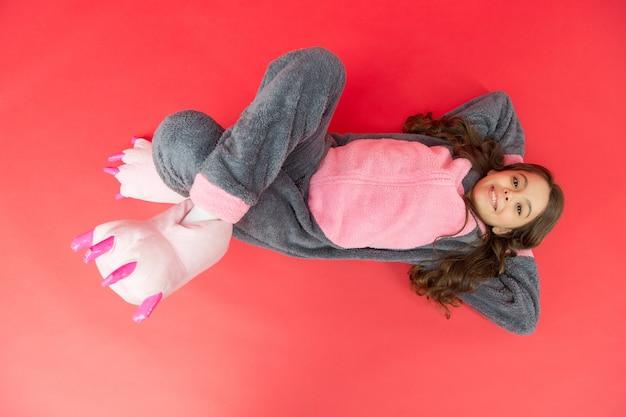 Konijn totem is symbool van geluk. ontspannen op verdieping bovenaanzicht. rust en ontspan. leuk konijntje. baby dier karakter. meisje in konijntjeskostuum. kind konijn kigurumi. een vrolijke pyjama met een meisjeskonijntje. glimlachend kind.