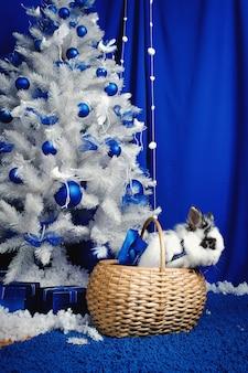 Konijn zit onder een kerstboom met cadeautjes