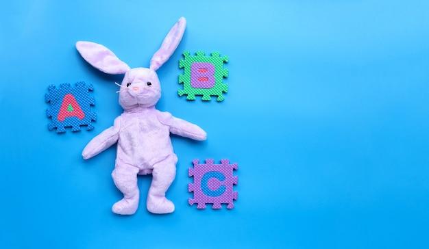 Konijnstuk speelgoed met engelse alfabetpuzzel op blauwe achtergrond. onderwijs concept, kopie ruimte