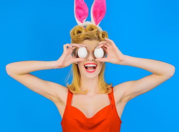 Konijntjesmeisje met witte eieren. gelukkig pasen. grappige vrouw in konijnenoren. ei versieren.