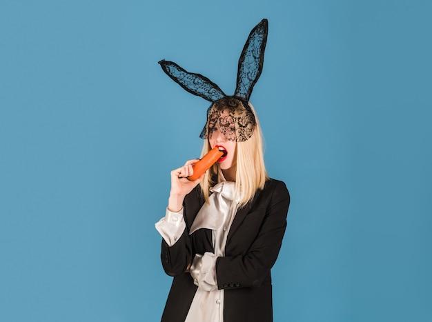 Konijntjesvrouw met wortel. pasen konijn meisje met zwarte oren.