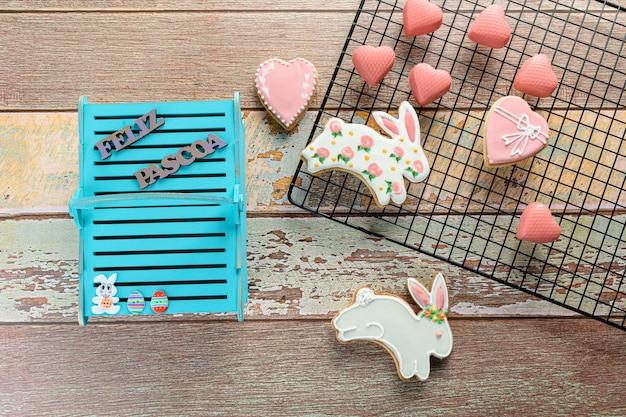 Konijnvormige koekjes omgeven door hartvormige koekjes, witte chocolade met roze eetbare verf en een blauwe houten mand in het portugees geschreven: vrolijk pasen.